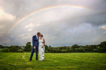 Wedding couple caught under a rainbow