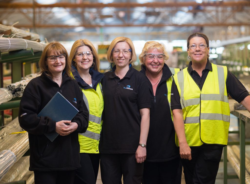 Group of women posing for photo at work